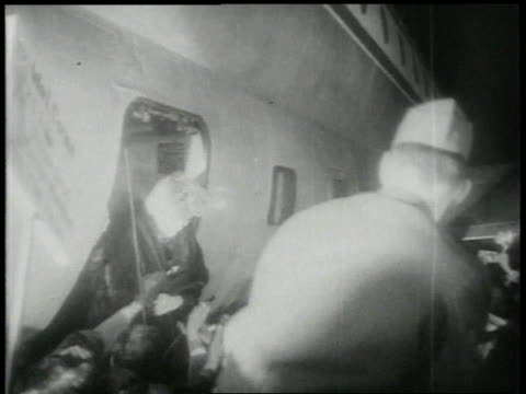 February 4 1954 WS Police hold back crowd as Joe DiMaggio and Marilyn Monroe exit the plane amidst flash photography / Tokyo Japan