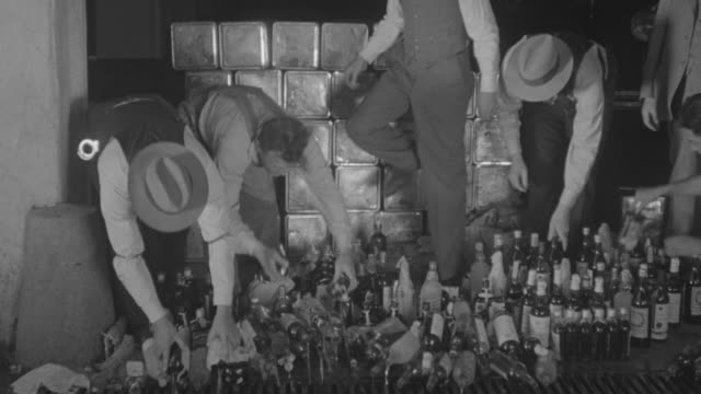 vídeos de stock, filmes e b-roll de ms pan tu td federal agents pouring out liquor bottles by case during prohibition era - criminoso