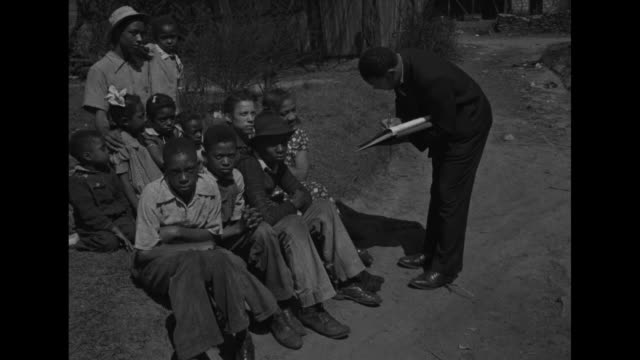 a federal census leans to interview an african american family and write in a ledger book / worker writes in book while talking to woman and children... - georgia stati uniti meridionali video stock e b–roll