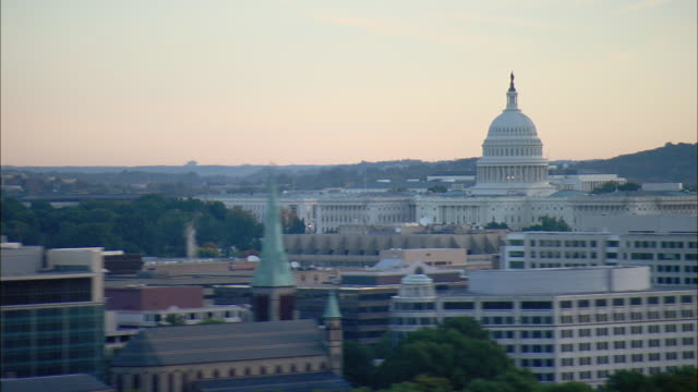 vidéos et rushes de aerial federal office buildings with u.s. capitol dome in distance, washington d.c., usa - style néoclassique