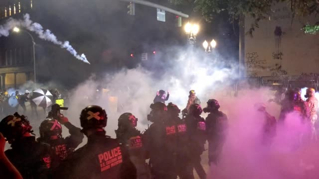 federal officers fire less-lethal rounds and tear gas into the crowd during a protest against racial injustice and police brutality in front of the... - portland oregon stock videos & royalty-free footage