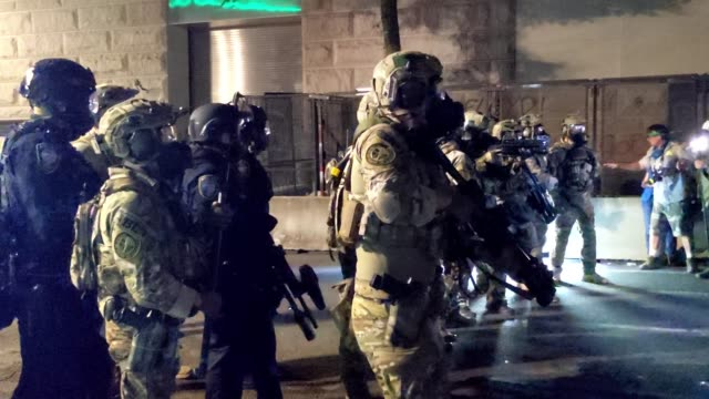 federal officers form a police line in front of the mark o hatfield us courthouse in the early hours of july 30 2020 in portland oregon protests... - portland oregon video stock e b–roll