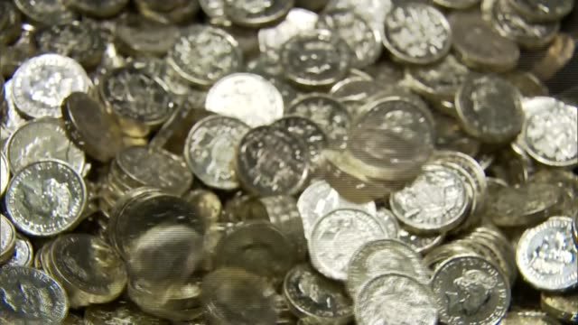federal reserve raises interest rates for the first time in nine and a half years; wales: royal mint: int pound coins falling into pile - 王立鋳貨局点の映像素材/bロール