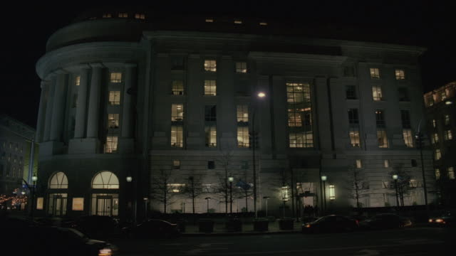pan federal trade commission building at night, with traffic and lights glowing in the windows / washington, d.c., united states - federal building stock videos and b-roll footage