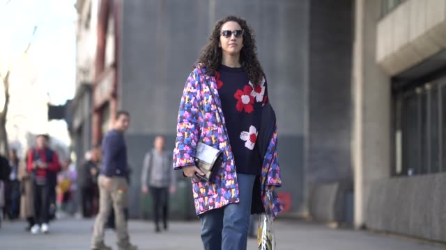 Federica Caiazzo wears a multicolor floral print puffer jacket a bag a floral print wool pullover blue denim cropped pants silver shoes sunglasses...