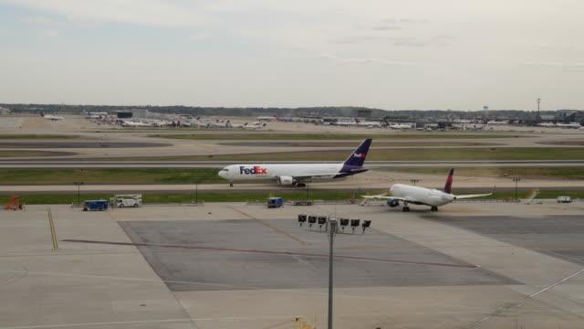 vidéos et rushes de fedex plane taxiing at the atlanta international airport terminal - aerospace