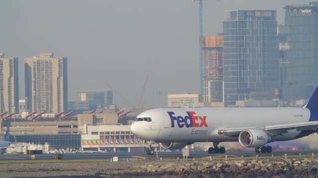 fedex plane taxiing in the boston logan international airport in the morning amidst the 2020 global coronavirus pandemic. - massachusetts stock videos & royalty-free footage