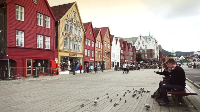 stockvideo's en b-roll-footage met feeding birds at bryggen old town in bergen - voeren