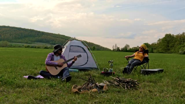 spüren sie die musik in der natur. camping in der natur. spielen sie gitarre. - musiker stock-videos und b-roll-filmmaterial