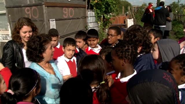 profile of Leyla Laksari Schoolchildren crowded around Leyla Schoolchildren planting seedlings in raised vegetable bed
