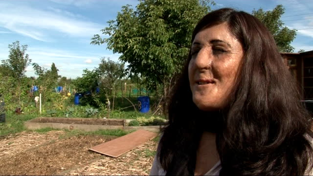profile of Leyla Laksari Woman holding up bunch of grapes grown on community allotment Vox pop Local allotment volunteer Allotment volunteers