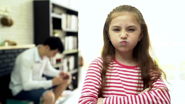 vídeos de stock, filmes e b-roll de sentindo-se solitário naqueles momentos. o jovem ocupado trabalhando no laptop e falando no telefone celular com sua filha sentado no primeiro plano e olhar triste. - ignorando