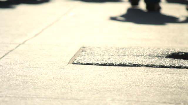 feet and shadows walking on sidewalk - människolem bildbanksvideor och videomaterial från bakom kulisserna