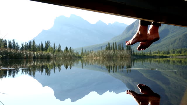 feet dangle from mountain boardwalk at sunrise, above lake - hanging stock videos & royalty-free footage