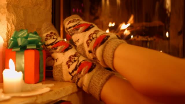 stockvideo's en b-roll-footage met voeten meisje met warme sokken bij de open haard - sfeervol