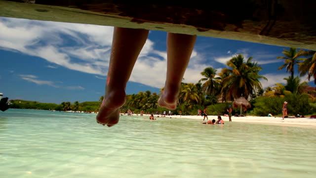 Feet hanging off pier on a beautiful desert island