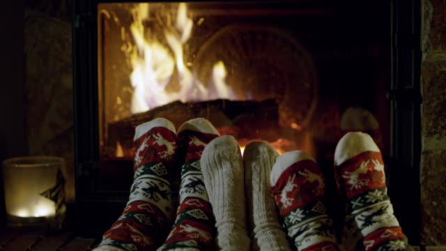 4k feet in cozy christmas socks relaxing by fireplace, real time - winter video stock e b–roll