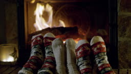 4K Feet in cozy Christmas socks relaxing by fireplace, real time