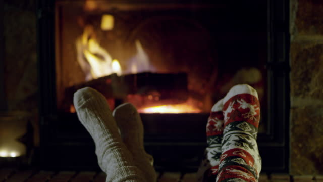 4k feet in cozy christmas socks relaxing by fireplace, real time - sock stock videos & royalty-free footage