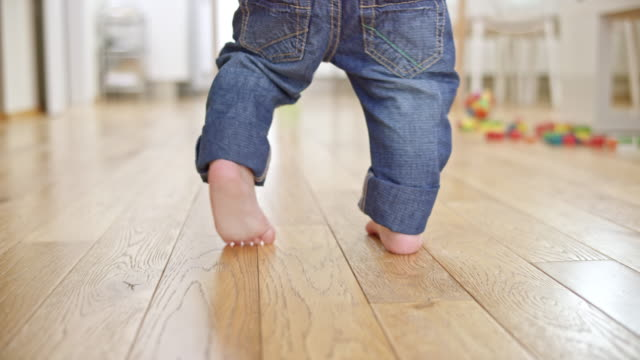 slo mo feet of a baby taking his first steps - primi passi video stock e b–roll