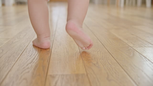 slo mo feet of a baby walking across a wooden floor - primi passi video stock e b–roll