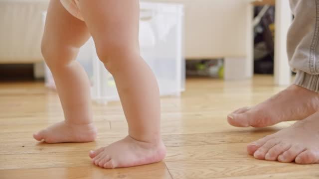 vídeos de stock, filmes e b-roll de slo mo pés de um bebê com os pés descalços, dando os primeiros passos - ensinando