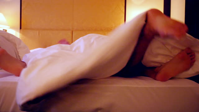 vídeos de stock e filmes b-roll de feet of a couple sharing a bed in a hotel - cama