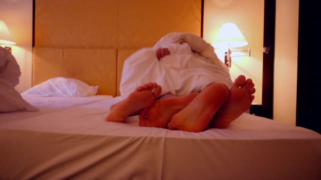 feet of a couple sharing a bed in a hotel - sensuality stock videos & royalty-free footage
