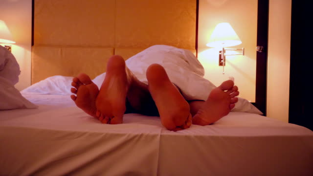 feet of a couple sharing a bed in a hotel - love making stock videos & royalty-free footage