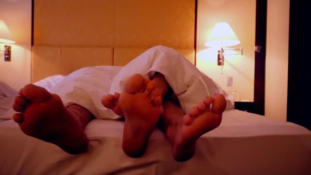 vídeos de stock, filmes e b-roll de pés de um casal dividindo a cama em um hotel - quarto de hotel