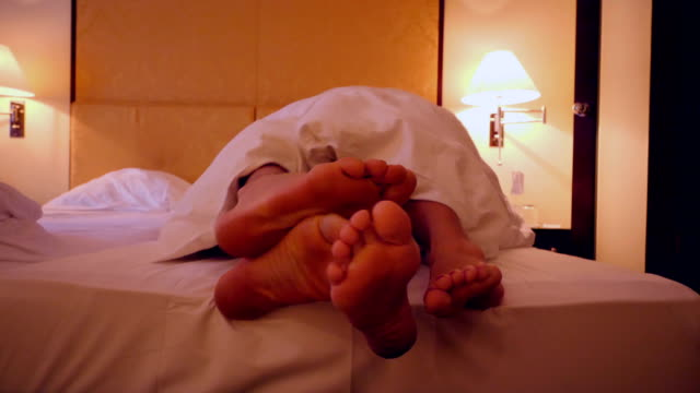 feet of a couple sharing a bed in a hotel - sexual issues stock videos & royalty-free footage
