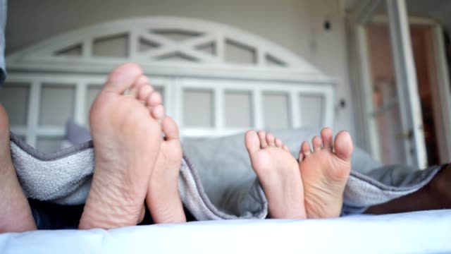 feet of a family lying in bed together - kids feet tickle stock videos & royalty-free footage