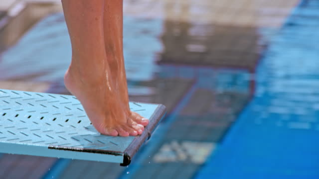 slo mo feet of a female diver jumping off the spring board and into the pool - primo piano a fuoco video stock e b–roll