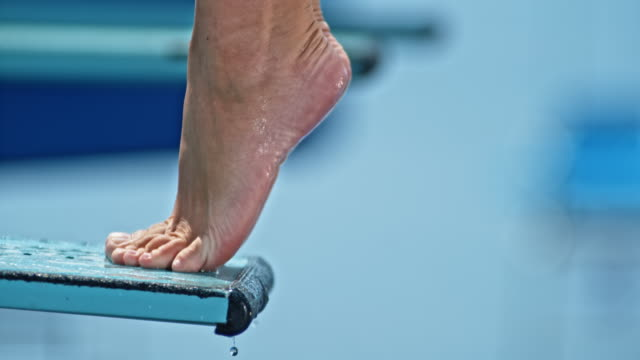 slo mo feet of a female high diver standing on the end of the diving board - balance stock videos & royalty-free footage