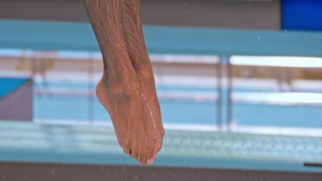 vidéos et rushes de slo mo pieds d'un plongeur mâle sauter haut dans l'air sur le panneau de ressort et de plonger dans la piscine - croatie