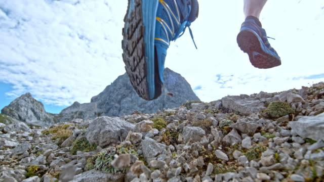 vidéos et rushes de pieds de rampe de vitesse d'un coureur masculin en cours d'exécution sur la montagne provoquant de gravier ou de nuages de points - endurance