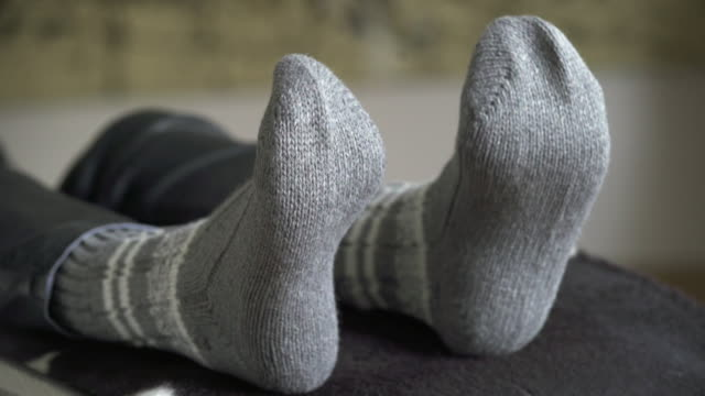 feet of a relaxing woman moving to music (4k/uhd) - sock stock videos & royalty-free footage