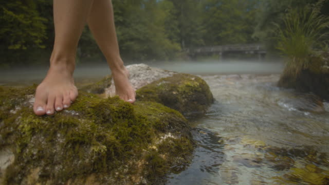 slo mo feet of a woman stepping over rocks in the river - moss stock videos & royalty-free footage