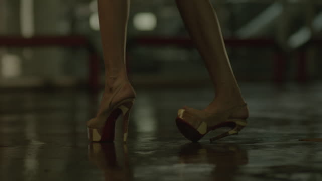 vídeos de stock e filmes b-roll de feet of a woman walking in car park basement while her high heel breaks. - sapato