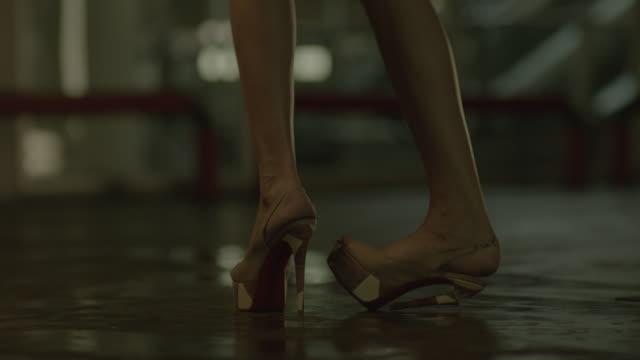 feet of a woman walking in car park basement while her high heel breaks. - high heels stock videos & royalty-free footage