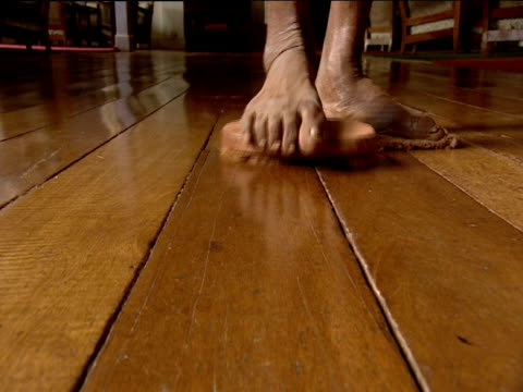 Feet of cleaner scrubbing and polishing wooden floor by standing on brush and cloth Munnar India