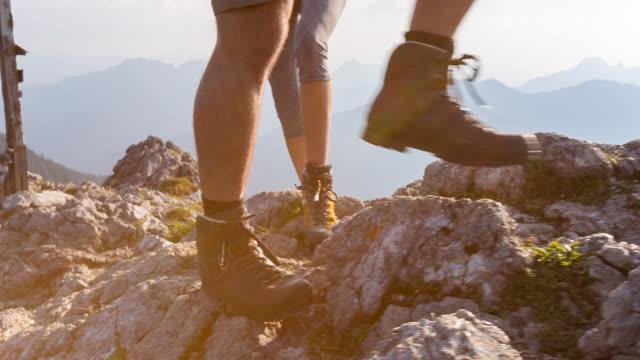 feet of couple climbing mountain summit, close up - bayern stock-videos und b-roll-filmmaterial