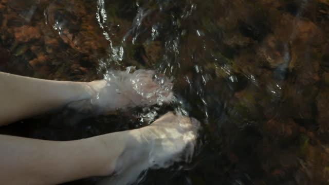 CU Feet of girl (8-9) sitting by creek / Sedona, Arizona, USA