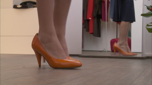 CU Feet of girl (10-11) trying on too big high heel shoes in fitting room / Brussels, Belgium