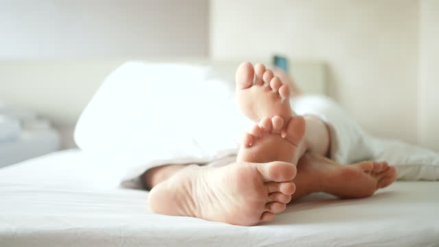feet of loving couple on bedroom in the morning - husband stock videos & royalty-free footage