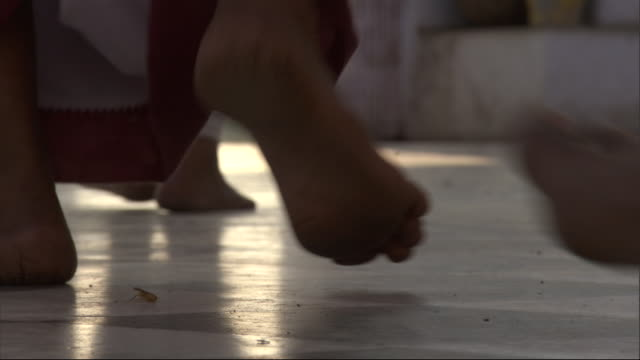 Feet of men walking through temple ringing hanging bells, Bateshwar Available in HD.