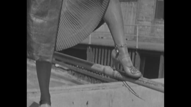 feet of passersby as they walk on boardwalk in unidentified area/ cu woman models her shoes ankle bracelet on one foot // high shot throngs of... - pelliccia materiale tessile video stock e b–roll
