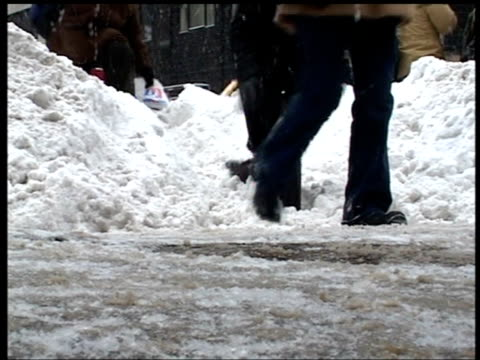 Feet of pedestrians stumble through snow drifts and slush in wake of blizzard Manhattan