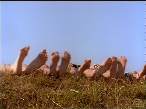 vídeos y material grabado en eventos de stock de feet of people lying on ground swishing back + forth outdoors - planta del pie