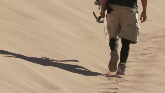 cu feet of person with sandboarder walking slowly up on sand dune / san pedro de atacama, norte grande, chile   - newoutdoors stock videos & royalty-free footage